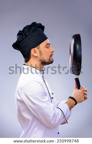 Cooking is his perfection. Side view portrait of handsome cook looking at his frying pan while standing over grey background with copy space - stock photo