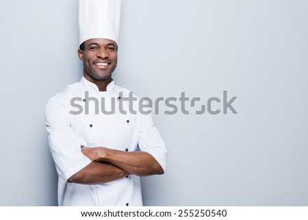 Cooking is my passion. Confident young African chef in white uniform keeping arms crossed and smiling while standing against grey background - stock photo