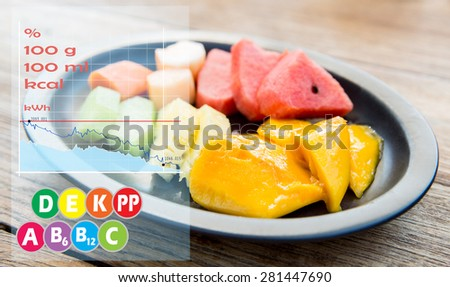 cooking, kitchen and food concept - plate of fresh juicy fruits with calories and vitamin chart - stock photo
