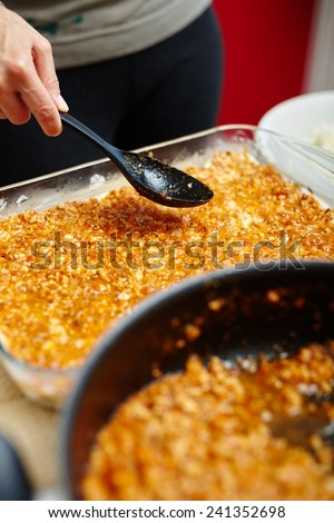 Cooking lasagna, putting grind meat recipe filling in the tray - stock photo