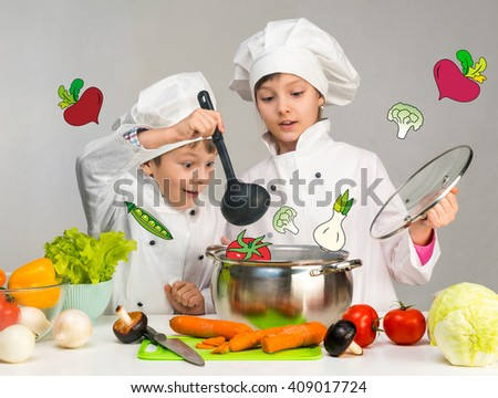 cooking little boy and girl looking in pan on table with vegetables