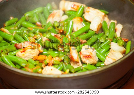 Cooking meat with green beans in fried pan