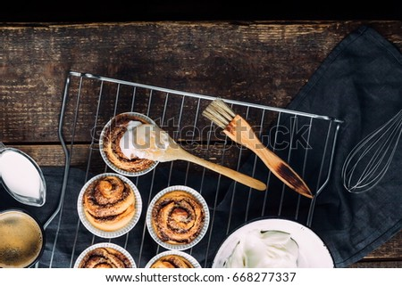 Cooking of homemade cakes. Sweet pastries on a wooden table with a cup of coffee and milk. Home Cinnabon. View from above. Rustic