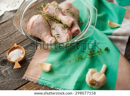 cooking of raw fresh chicken legs with garlic and herbs - stock photo