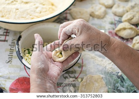 Cooking of russian pirozhki, woman's hands putting filling (eggs and spring onion) in a yeast dough. Pirozhki are traditional fried buns stuffed with a variety of fillings.