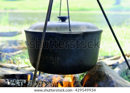 Cooking outdoors. Cauldron on a fire in the forest - stock photo