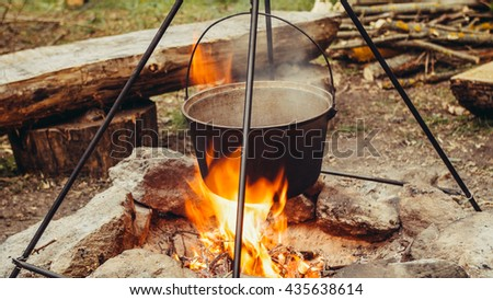 Cooking outdoors in cast-iron cauldron. Cooking meat on a fire. Food in a cauldron on a fire. Cooking food in nature on the cauldron. - stock photo