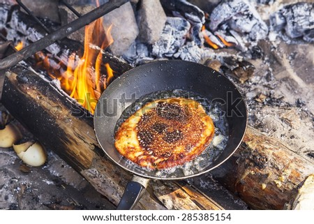 Cooking pancakes on a griddle in field conditions - stock photo