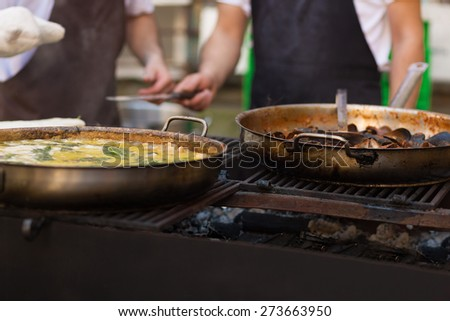 Cooking pasta and mussels in the street food festival - stock photo