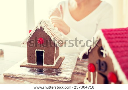 cooking, people, christmas and decoration concept - happy woman making gingerbread houses at home