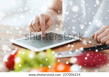 cooking, people, technology and home concept - close up of man reading recipe from tablet pc computer and vegetables on table in kitchen - stock photo