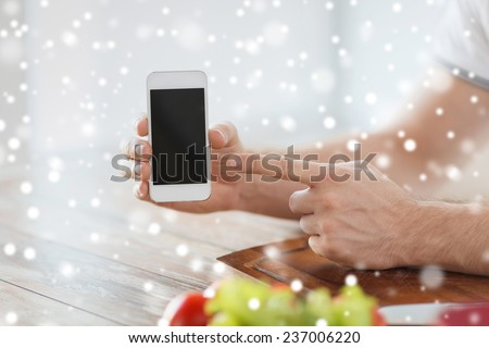 cooking, people, technology and home concept - close up of man with vegetables on table showing blank smartphone screen in kitchen - stock photo