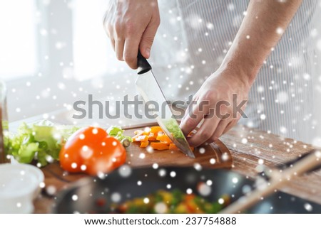 cooking, people, vegetarian food and home concept - close up of man chopping paprika and other vegetables on cutting board with big knife - stock photo
