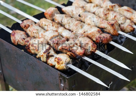 cooking pork shashlik  on skewer, in brazier outdoors - stock photo
