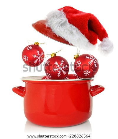 Cooking pot with Christmas ornaments and santas hat - stock photo