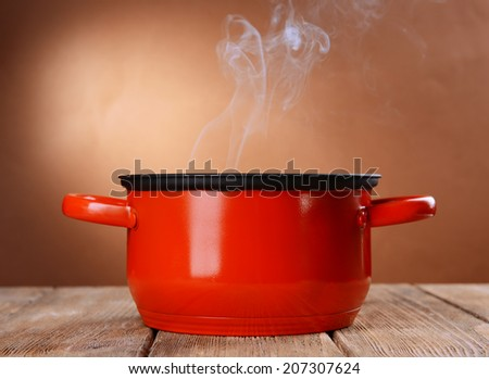 Cooking pot with steam on table on brown background