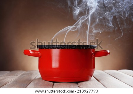 Cooking pot with steam on table on brown background - stock photo