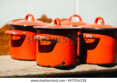 Cooking pots with lids orange enamel old outdoor on sunny day on wooden background - stock photo