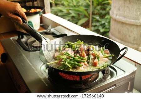 cooking preparing , stew pork with spices and herbs in home kitchen - stock photo