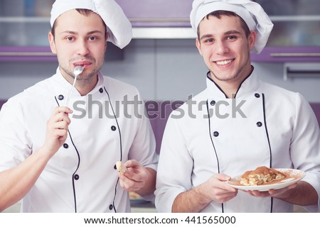 Cooking process concept. Portrait of two funny working men in cook uniform tasting and presenting their dessert in modern kitchen. Indoor shot