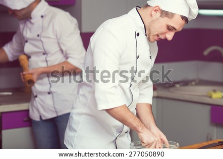 Cooking process concept. Portrait of two working men in cook uniform making food in modern kitchen. Indoor shot - stock photo