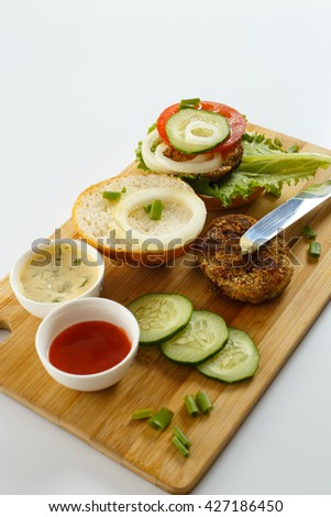 Cooking process of a sandwich burger, ingredients on wooden cutting board on wooden table against white background, fresh vegetables, herbs, fried meat, buns, sauces and knife, shallow DOF - stock photo