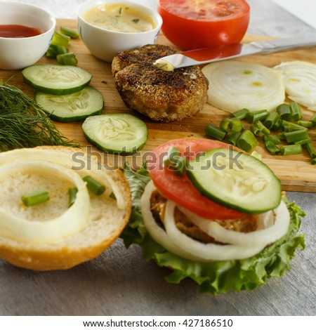 Cooking process of a sandwich burger, ingredients on wooden cutting board on wooden table against white background, fresh vegetables, herbs, fried meat, buns, sauces and knife, close up, shallow DOF - stock photo