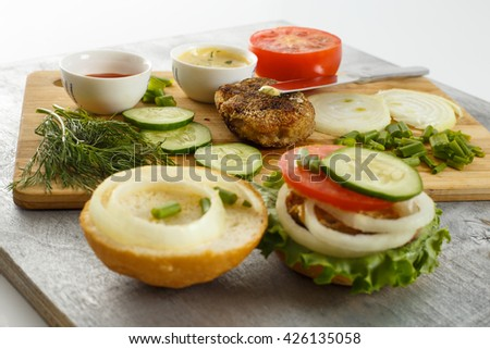Cooking process of sandwich burger, ingredients on cutting board on wooden table against white background, fresh vegetables, herbs, fried meat, buns, sauces and knife, horizontal view, shallow DOF - stock photo