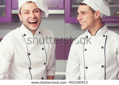 Cooking process, perfect teamwork concept. Portrait of two working men in cook uniform making food in modern kitchen. Indoor shot