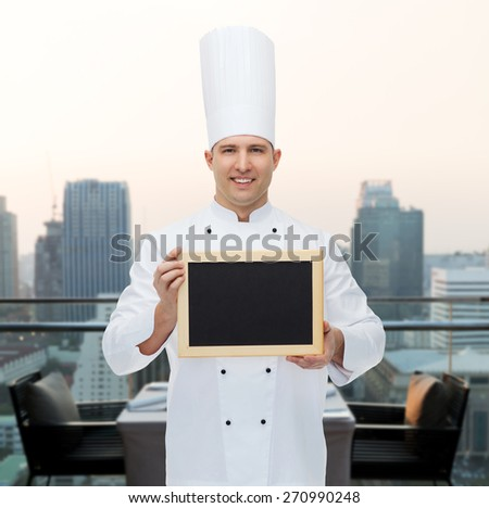 cooking, profession, advertisement and people concept - happy male chef cook showing and holding blank menu board over city restaurant lounge background - stock photo