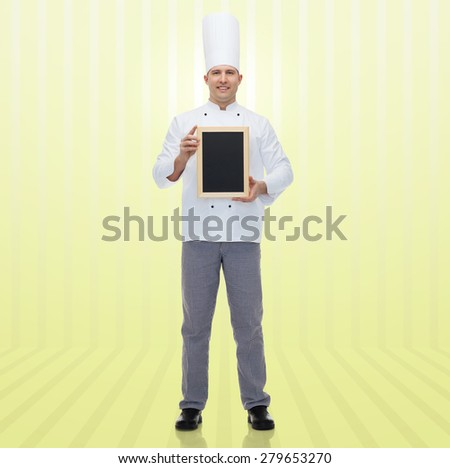 cooking, profession, advertisement and people concept - happy male chef cook showing and holding blank menu chalk board over yellow background - stock photo