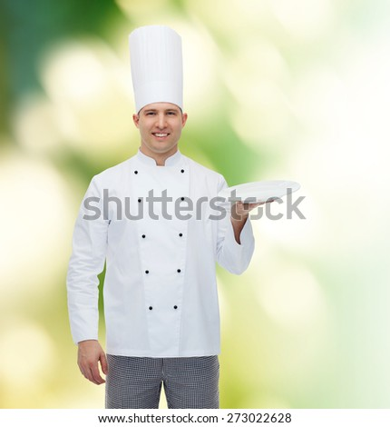cooking, profession, advertisement and people concept - happy male chef cook showing something on empty plate over green background