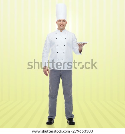 cooking, profession, advertisement and people concept - happy male chef cook showing something on empty plate over yellow background - stock photo
