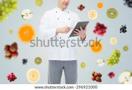 cooking, profession and people concept - close up of happy male chef cook holding tablet pc computer over fruits and berries on gray background - stock photo
