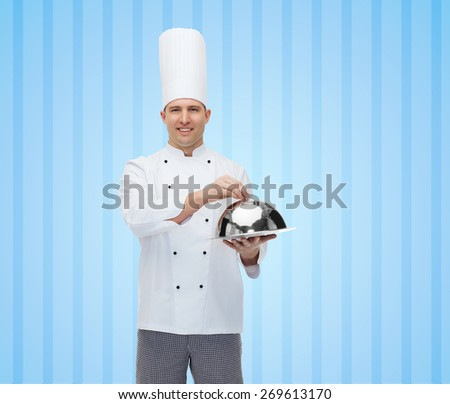 cooking, profession and people concept - happy male chef cook holding cloche over blue striped background - stock photo