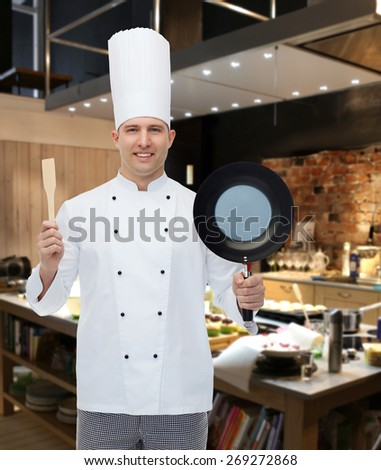 cooking, profession and people concept - happy male chef cook holding frying pan and spatula over restaurant kitchen - stock photo