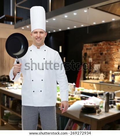 cooking, profession and people concept - happy male chef cook holding frying pan over restaurant kitchen - stock photo