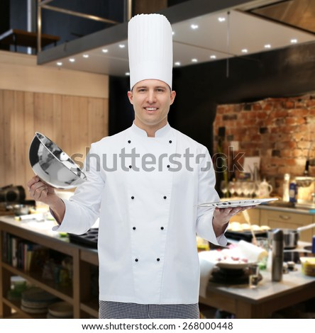 cooking, profession and people concept - happy male chef cook opening cloche cover over restaurant kitchen - stock photo