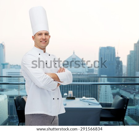 cooking, profession and people concept - happy male chef cook with crossed hands over city restaurant lounge background - stock photo
