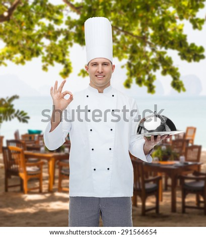 cooking, profession, gesture and people concept - happy male chef cook holding cloche and showing ok sign over restaurant lounge on beach - stock photo