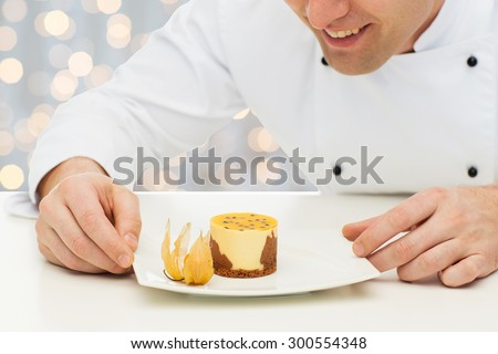 cooking, profession, haute cuisine, food and people concept - close up of happy male chef cook decorating dessert over holidays lights background - stock photo