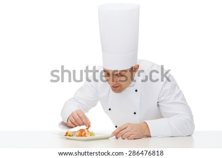 cooking, profession, haute cuisine, food and people concept - happy male chef cook decorating dish - stock photo