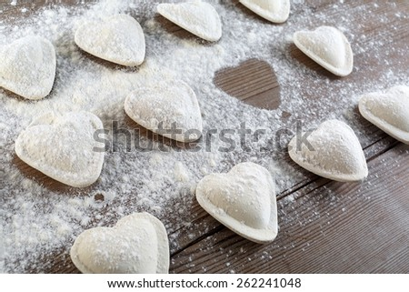 Cooking ravioli. Raw dumplings in the form of hearts sprinkled flour on wooden background closeup. Shallow depth of field. - stock photo