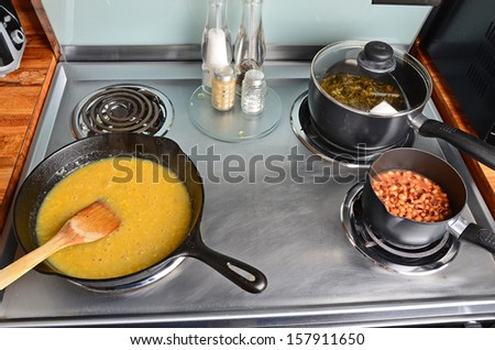 Cooking soul food with creamed corn in cast iron skillet; black eyed peas in small sauce pan and collard greens in medium sauce pan with lid -- all simmering on stainless steel electric range. - stock photo