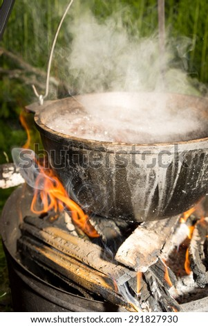 Cooking soup in a pan over campfire. - stock photo