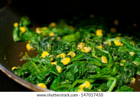 Cooking spinach, garlic and corn salad on frying pan - stock photo