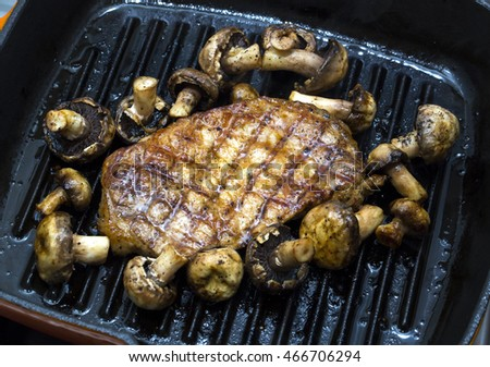 Cooking steak and vegetables on grill pan