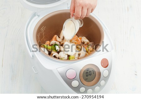 cooking stew of salmon with vegetables and cream sauce in multicooker - stock photo