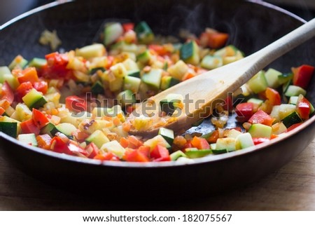 Cooking stew ratatouille from vegetables in frying pan, delicious vegetarian french dish