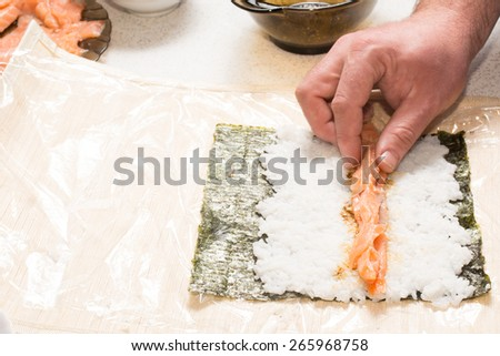 Cooking sushi at home with nori, salmon, rice - stock photo